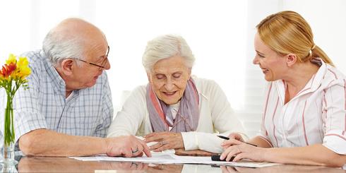 Zwei glückliche Senioren bei einer Finanzberatung diskutieren den Vertrag
